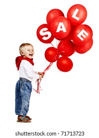 cute little boy in white shirt, jeans and red scarf laughing as he holds a bunch of red balloons with sale sign.