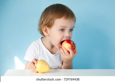 Cute little boy in white shirt sitting at the table and eats fruits - red Apple and yellow pear.