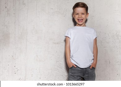 Cute little boy in white T-shirt posing in front of grunge concrete wall. Portrait of fashionable male child. Smiling boy posing, gray wall on background. Concept of children style and fashion. - Shutterstock ID 1013665297