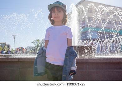 Cute little boy in a white t-shirt walks down the street.
