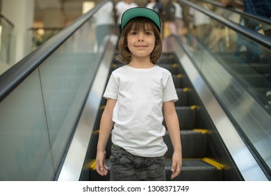 Cute little boy in white t-shirt on an escalator.