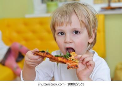 cute little boy in white tshirt eats pizza