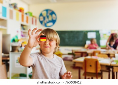 Cute little boy working in classroom, holding self made german flag, primary education