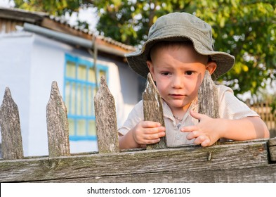 Cute little boy with a worried expression clinging to an old slatted wooden fence in his sunhat waiting for Dad to come home