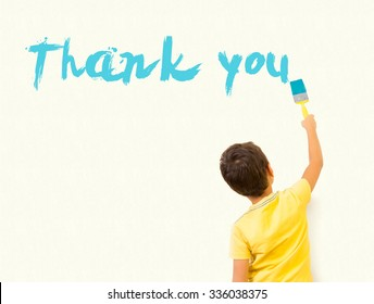 "Cute little boy writing ""Thank You"" with painting brush on wall background"