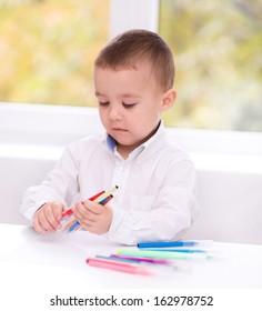 Cute little boy is writing using a pen in preschool