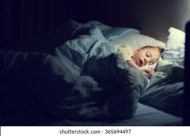 Cute little boy in yellow pyjamas is sweetly sleeping in bed with blue bed-clothes. Image with selective focus and toning