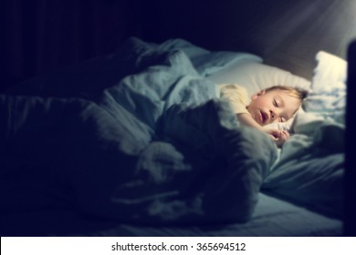 Cute little boy in yellow pyjamas is sweetly sleeping in bed with blue bed-clothes. Image with selective focus, toning and soft effects of shining light.