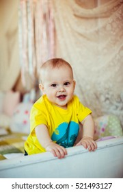 cute little boy in a yellow t-shirt sits on the bed