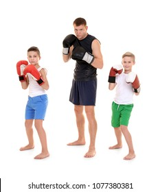 Cute little boys in boxing gloves and their coach on white background