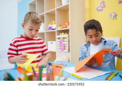Cute little boys cutting paper shapes in classroom at the nursery school