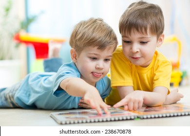 Cute little boys at home reading a book