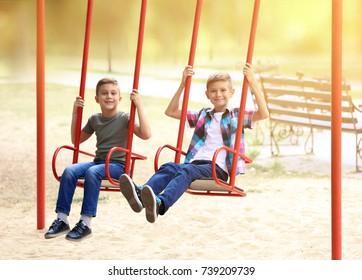 Cute little boys on swings in park