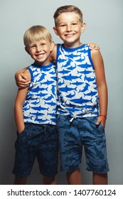 Cute little boys in white and blue sleeveless shirts posing in front of gray background. Portrait of fashionable male childs. Smiling kids posing, hugging. Concept of children style and fashion