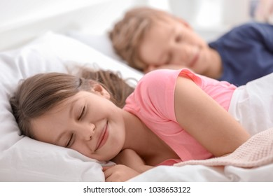 Cute little brother and sister sleeping in bed at home