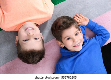 Cute little brothers lying on colourful carpet at home