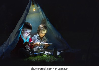 Cute little brothers, playing on tablet and telephone at night in campside, in the tent