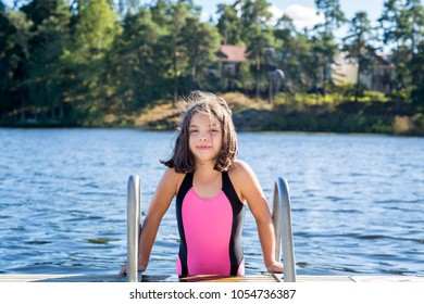 Cute little brown haired girl in swimsuit about to climb down in the water to swim.