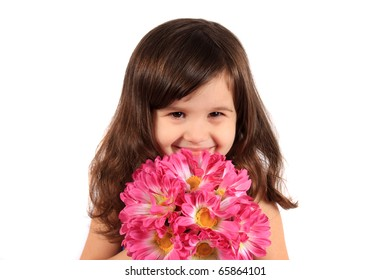Cute little brunette three year old girl holding and hiding behind flowers and smiling on a white background