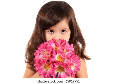 Cute little brunette three year old girl holding and hiding behind flowers being shy on a white background
