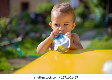 cute little caucasian baby eating fruit puree in pouch and looking into the camera in front of the yellow table. close up, on the background is  a green garden on a sunny day in blur