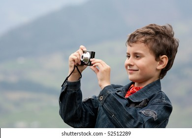 Cute little caucasian boy taking photos outdoor