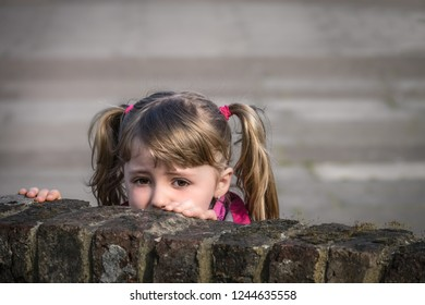 Cute little Caucasian girl looking scared and hiding behind brick wall