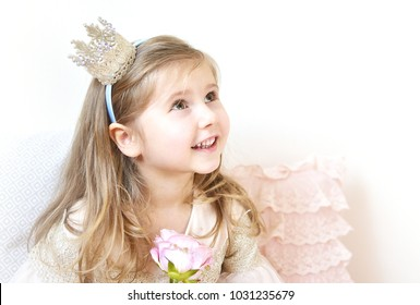 Cute Little Caucasian Girl in Pastel Pink Dress Princess Preparing for Birthday Party Concept Queen Crown on Head Springtime