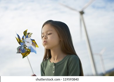 Cute little Caucasian girl playing with paper windmill