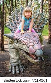 Cute little caucasian girl riding on Ankylosaurus dinosaur in summer