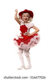 Cute little caucasian girl wearing red skirt, t-shirt with flowers and cowboy hat isolated on white background. She is dancing