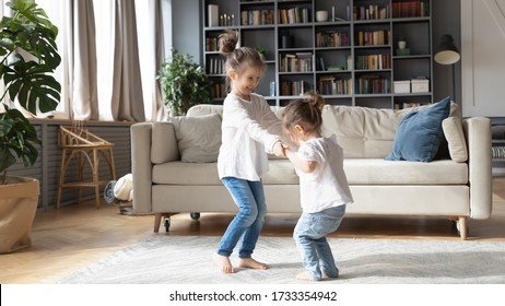 Cute little Caucasian girls sisters hold hands dancing in cozy living room together, small preschooler children play have fun at home, jumping and swirling engaged in funny childish activity