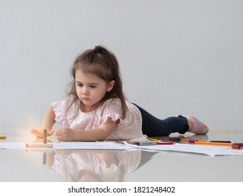Cute little Caucasian toddler girl lying on the floor using crayons and colorpencils coloring on the papers.