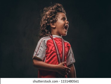 Cute little champion boy in sportswear with gold medal enjoying the victory. Isolated on a dark textured background.
