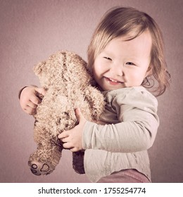 Cute little cheerful mixed race Asian baby girl In her hand she carries a teddy bear brown color, soft toned