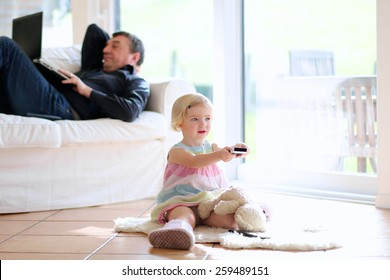 Cute little child, 3 years old preschooler girl watching tv sitting on the tiles floor, her father lying comfortable with laptop on sofa - happy family at home