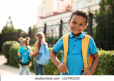 Cute little child with backpack outdoors. Elementary school
