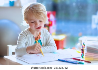 Cute little child, blonde preschooler girl is drawing and painting with colorful felt-tip pens at home or kindergarten sitting at small table in bright sunny playroom