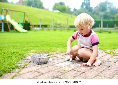 Cute little child, blonde toddler girl playing outdoors sitting at terrace at the backyard of the house drawing or painting with colorful chalk. Big green garden at the background