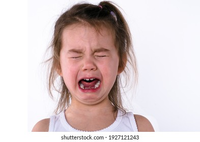 Cute little child is crying on a white background. Сlose-up portrait of a crying baby