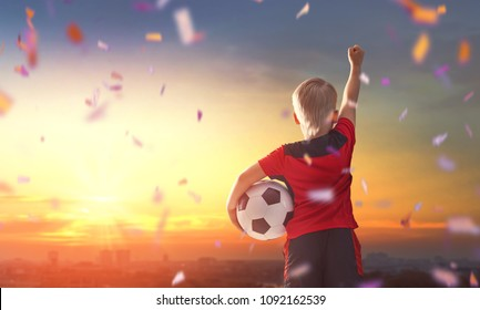 Cute little child dreaming of becoming a soccer player. Boy playing football on sunset.