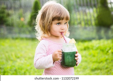 Cute little child drinks healthy green smoothie with straw in a jar mug against the background of greenery outdoor.