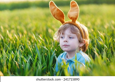 Cute little child with Easter bunny ears playing in green grass on sunny spring day, celebrating Easter holiday