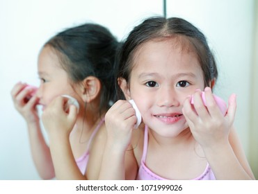 Cute little child girl applying makeup on face with Sponge Powder Puff near a mirror.