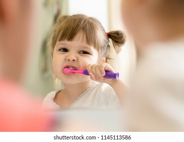 Cute little child girl brushing teeth and looking in mirror in bathroom