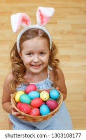A cute little child girl with bunny ears sits on the floor with a basket of Easter eggs.