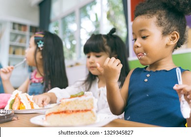 cute little child girl with diversity friends eating cake together. kids eat dessert .