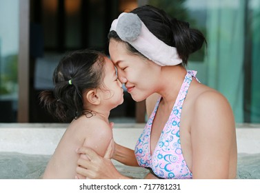 Cute little child girl and her mother in hot tub.