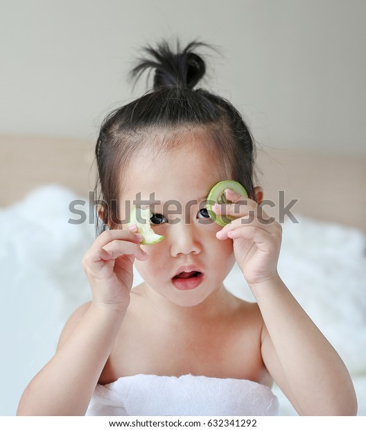 Cute little Child girl holding cucumber slices on her face, concept for skin care.