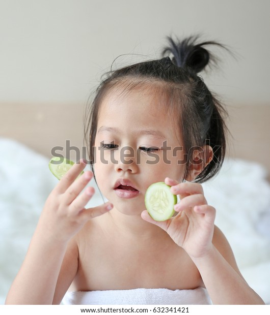 Cute little Child girl holding cucumber slices, concept for skin care.